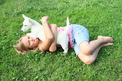 Little girl lying with a puppy Royalty Free Stock Photos