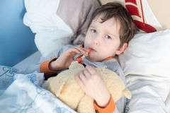 Little boy lying sick in bed Royalty Free Stock Image