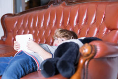 Little boy lying on sofa with tablet and panda toy Stock Image