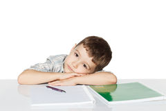 Little boy lying on the table with exercise books Royalty Free Stock Photo
