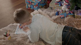 Little boy lying under christmas tree and write a letter to santa claus stock video