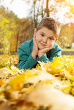 Little boy lying on the yellow leaves in the autumn park Stock Images