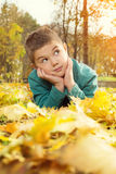Little boy lying on the yellow leaves in the autumn park Royalty Free Stock Photography