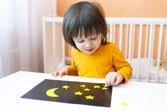 Little boy made night sky and stars of paper details Stock Images