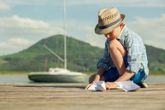 Little boy make paper boats sitting on the wooden pier Royalty Free Stock Photos