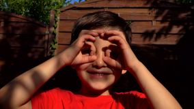 Little boy makes binoculars with his fingers. Little boy makes binoculars gesture with his fingers stock video