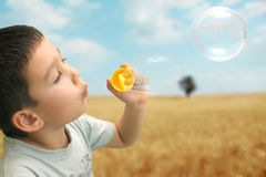 Little boy makes bubbles outdoor Stock Photo