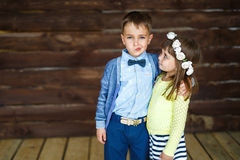 Little boy makes faces and his sister looks to him. Little brother makes faces and his sister looks to him Royalty Free Stock Photos