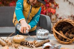 Children`s creative activity in autumn in the garden. A little boy makes scenery for Halloween. He paints pumpkins and bumps in the garden royalty free stock photos