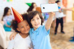 Little boy makes selfie with happy birthday girl in party hat at birthday party. Selfi`s birthday. Little children on birthday celebrations Royalty Free Stock Image