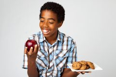 Little boy making decisions of eating healthy verses unhealthy. Stock Photos