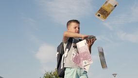 Little boy making euros banknotes fly.
