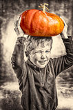 Little boy making a face with heavy orange pumpkin hat Stock Photo