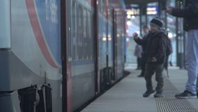Little boy making farewells at railway station, waving hand to friend on a train. Stock footage stock footage