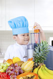 Little boy making fresh fruits juice Stock Photo