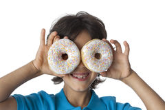 Little boy making fun with donuts. On white background Royalty Free Stock Photography