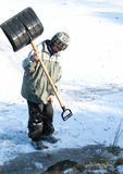Little boy making a hole in ice on pond Stock Photography