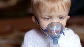 Little boy making inhalation with a nebulizer. stock video