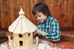 Little boy making the last finishing touches on a bird house Royalty Free Stock Image