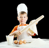 Little boy making pizza or pasta dough. Royalty Free Stock Images