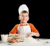 Little boy making pizza or pasta dough. Stock Photos