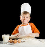 Little boy making pizza or pasta dough. Royalty Free Stock Image