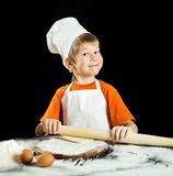 Little boy making pizza or pasta dough. Royalty Free Stock Photos