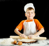Little boy making pizza or pasta dough. Stock Images