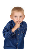 Little boy making silence gesture. Portrait of a cute little boy making silence gesture in denim blue shirt isolated on white background Royalty Free Stock Photography