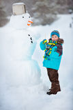 Little boy making a snowman Stock Photos