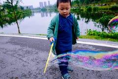 Little boy making soap bubbles Stock Photos
