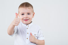 Little boy making thumbs up. Little boy in a white shirt making thumbs up by two fists with finger in the studio stock illustration