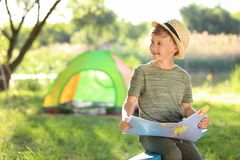 Little boy with map near tent outdoors. Ttle boy with map near tent outdoors. Summer camp stock photos