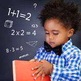 Little boy on math lesson. Holding in hands book and standing near blackboard with written mathematical equation, back to school Royalty Free Stock Photography