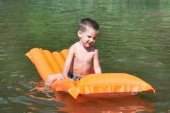 Little boy on mattress on water lake Royalty Free Stock Photo