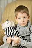 Little boy measures the temperature of the toy dog Stock Image