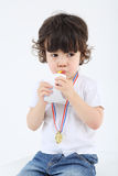 Little boy with medal on his chest sits and drinks juice Stock Photo