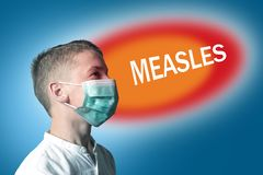 Little boy in a medical mask on a bright background with inscription MEASLES.  stock photography