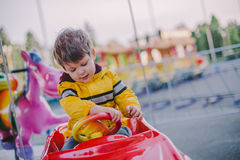 Little boy on the merry-go-round Stock Photos