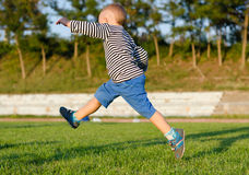 Little boy midair kicking a ball. Playing soccer on a sportsfield in evening sunlight Royalty Free Stock Image