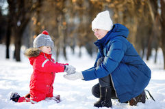 Little boy and middle age woman having fun with snow. Active outdoors family leisure with children in winter Royalty Free Stock Photo