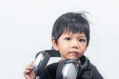 Little Boy mignon avec l'écouteur sur le fond blanc Image stock