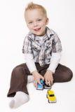 Little Boy mignon jouant avec ses jouets photos stock