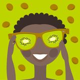 Little boy in mirrored sunglasses with a reflection of the kiwi. Funny little boy in adult mirrored sunglasses with reflection kiwi on a bright green background Stock Photo