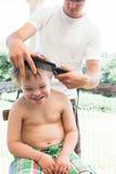 Little Boy mit dem Abstieg-Syndrom, das seinen Haarschnitt erhält Stockbilder