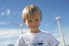Little Boy mit Windkraftanlagen im Hintergrund Stockfotografie
