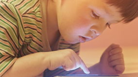 Little boy with mobile phone lying on a sofa stock video footage