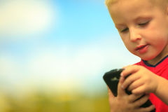 Little boy with mobile phone outdoor. Technology generation. Stock Photos