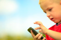 Little boy with mobile phone outdoor. Technology generation. Stock Photo