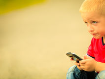 Little boy with mobile phone outdoor. Technology generation. Royalty Free Stock Photo
